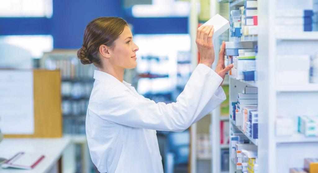 Pharmacist pulling medicine off a shelf